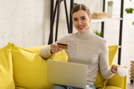 Smiling woman holding credit card, laptop and coffee cup on sofa at home