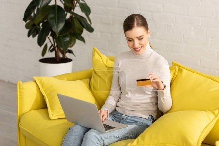 Smiling girl looking at credit card and using laptop on sofa