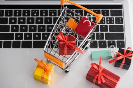 Photo for Top view of toy gift boxes with cart on laptop - Royalty Free Image