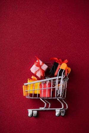 Photo pour Vue du dessus des cadeaux avec chariot à jouets sur fond rouge - image libre de droit