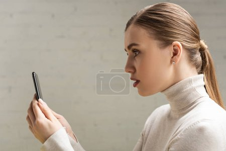 Photo for Side view of attractive woman holding smartphone - Royalty Free Image