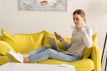 Photo pour Jeune femme boire du café tout en tenant la carte de crédit et en utilisant un ordinateur portable sur le canapé - image libre de droit
