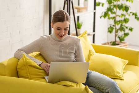 Photo for Beautiful smiling freelancer using laptop on sofa at home - Royalty Free Image