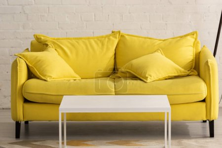 Yellow couch with cushions and white coffee table in living room