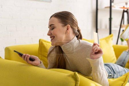 Photo pour Vue latérale d'une belle jeune femme souriante tenant une carte de crédit et un smartphone sur un canapé - image libre de droit