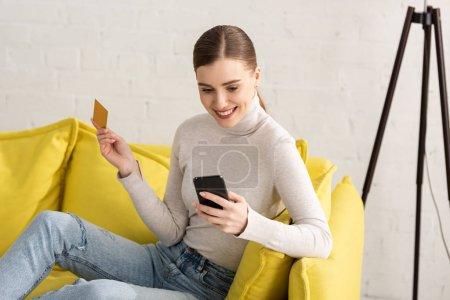 Photo pour Belle fille souriante utilisant un smartphone et tenant la carte de crédit sur le canapé à la maison - image libre de droit