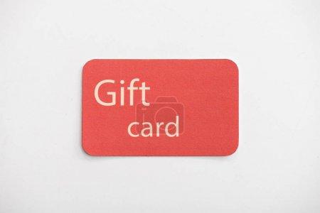 Photo pour Vue du haut de la carte-cadeau rouge sur la surface blanche - image libre de droit