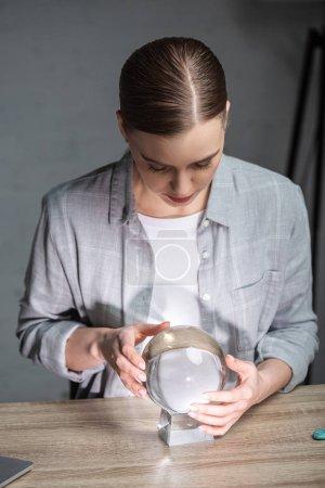Foto de Hermoso astrólogo utilizando bola de cristal en la mesa de madera. - Imagen libre de derechos