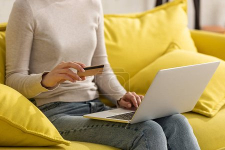 Photo for Cropped view of girl holding credit card and using laptop on sofa - Royalty Free Image
