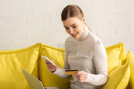 Beautiful smiling girl with laptop, credit card and smartphone on sofa at home
