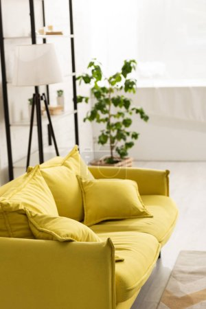 Comfortable yellow sofa with cushions in living room