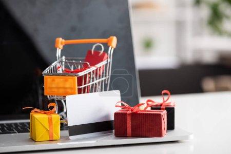 Foto de Enfoque selectivo de carritos de juguete y cajas de regalo con tarjeta de crédito en portátil en la mesa. - Imagen libre de derechos