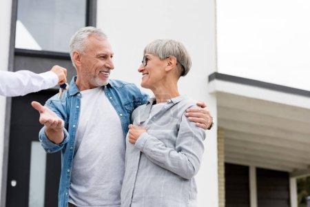 Photo pour Crochet vue d'un courtier donnant les clés d'une nouvelle maison à un homme et une femme mûrs souriants - image libre de droit