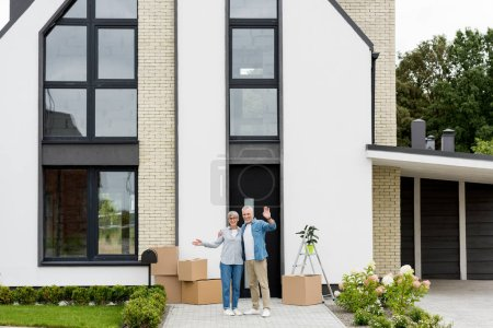 Photo for Smiling mature man and woman waving near new house - Royalty Free Image