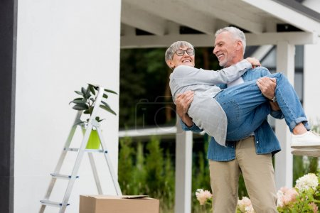 Photo for Mature man holding smiling woman in glasses near new house - Royalty Free Image