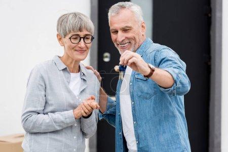 Photo pour Homme mûr tenant les clés de la nouvelle maison et femme souriante la regardant - image libre de droit