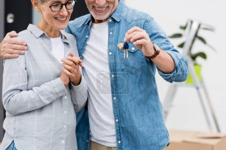 Photo pour Crocheté vue d'un homme mûr tenant les clés d'une nouvelle maison et d'une femme souriante la regardant - image libre de droit