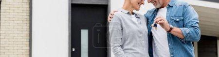 Photo pour Photo panoramique d'un homme mûr tenant les clés d'une nouvelle maison et d'une femme souriante et accolée - image libre de droit