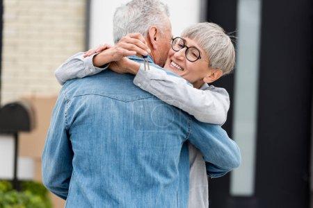 Photo pour Une femme souriante tenant les clés de la nouvelle maison et embrassant un homme mûr - image libre de droit