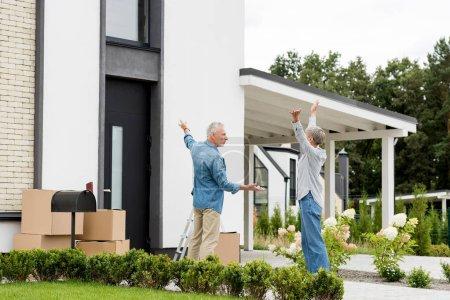 Photo pour Homme mûr pointant du doigt et tenant les clés de la maison neuve à la femme les mains tendues - image libre de droit
