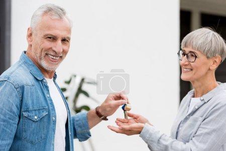 Photo pour Un homme d'âge mûr remet les clés d'une nouvelle maison à une femme souriante - image libre de droit