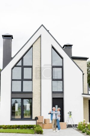 Photo for Mature man and smiling woman dancing and looking at each other near new house - Royalty Free Image