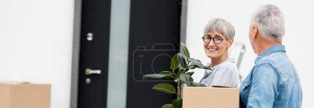 Photo pour Plan panoramique de l'homme mature tenant la boîte et la femme souriante tenant la plante près de la nouvelle maison - image libre de droit