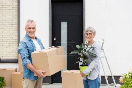 Photo pour Mature homme tenant boîte et souriant femme tenant plante près de nouvelle maison - image libre de droit