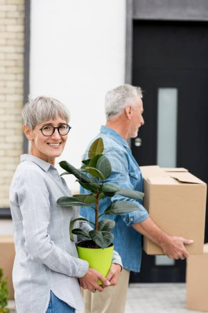 Photo for Selective focus of woman holding plant near and mature man holding box near new house on background - Royalty Free Image