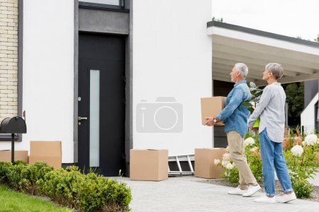 Photo for Mature man holding box and woman holding plant near new house - Royalty Free Image
