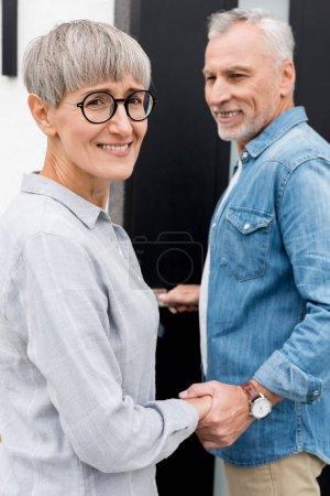 Photo pour Homme mature regardant femme souriante et entrant dans une nouvelle maison - image libre de droit