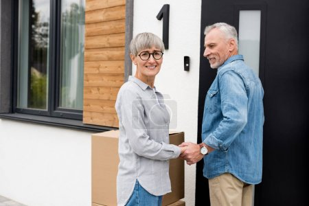 Photo for Mature man looking at smiling woman and holding hands with her new house - Royalty Free Image