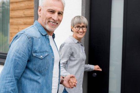 Photo pour Une femme souriante tenant la main d'un homme et entrant dans une nouvelle maison - image libre de droit