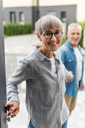 selective focus of smiling woman holding hands with man and entering to new house