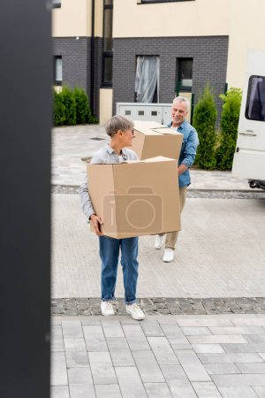 Photo for Mature man and smiling woman bringing boxes to new house - Royalty Free Image