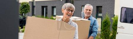 Photo pour Photo panoramique d'un homme mûr et d'une femme souriante apportant des boîtes à la nouvelle maison - image libre de droit