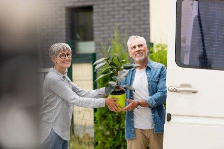Photo pour Homme mature et femme souriante tenant plante près de nouvelle maison - image libre de droit