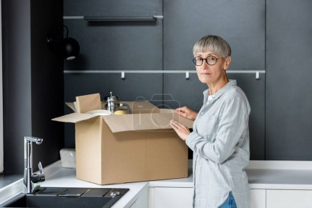 Photo for Mature woman unpacking box and looking at camera in new house - Royalty Free Image