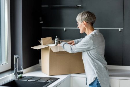 mature woman in glasses unpacking box in new house