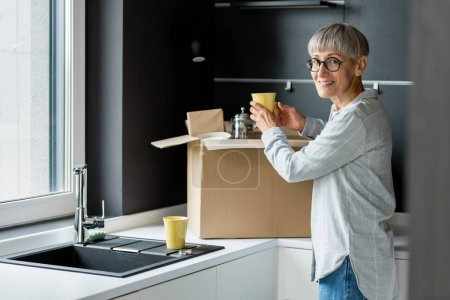 Photo for Smiling mature woman unpacking box in new house - Royalty Free Image