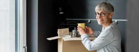 Photo for Panoramic shot of smiling mature woman unpacking box in new house - Royalty Free Image