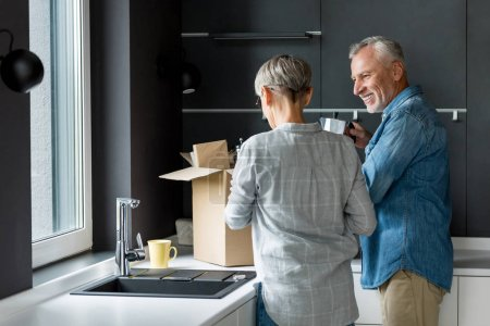 Photo for Smiling man and woman unpacking box in new house - Royalty Free Image