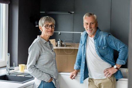 Photo pour Sourire homme et femme regardant caméra dans une nouvelle maison - image libre de droit