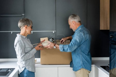 Photo for Side view of mature man and smiling woman unpacking box in new house - Royalty Free Image
