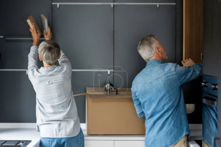 Photo for Back view of mature man opening door and woman arranging books in new house - Royalty Free Image