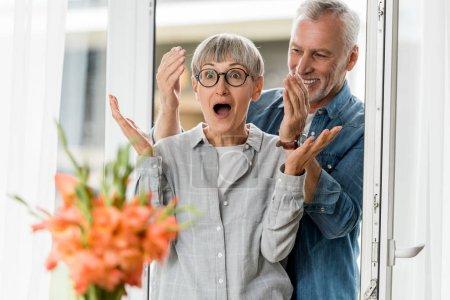 Photo pour Foyer sélectif de souriant homme et femme choquée regardant bouquet dans la maison neuve - image libre de droit