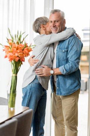 Photo pour Mature femme étreignant sourire et bel homme dans nouvelle maison - image libre de droit