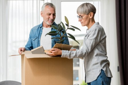 Photo for Smiling man and mature woman unpacking box in new house - Royalty Free Image