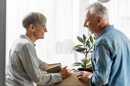 Photo pour Side view of smiling man and mature woman unpacking box in new house - image libre de droit