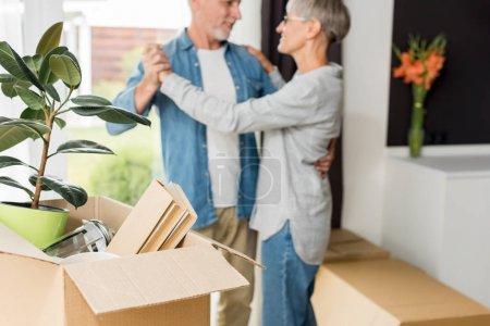 Photo pour Focalisation sélective de boîte avec plante et livres et un couple mûr dans la nouvelle maison sur l'arrière-plan - image libre de droit